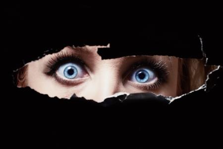 Blue eyes of a young woman peeping through a hole Standard-Bild