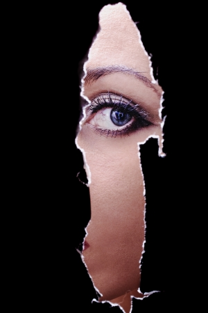 One eye of a young woman spying through a hole in the wall Stock Photo