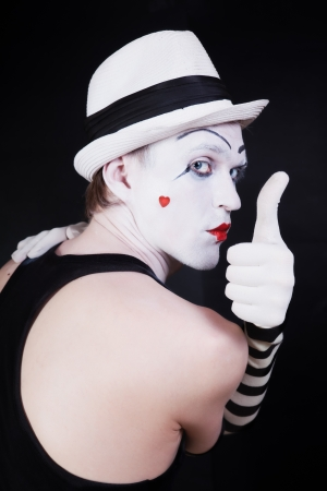Theater actor with mime makeup on a black background photo