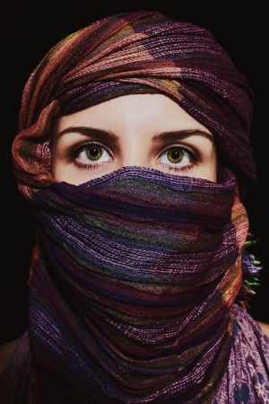 Portrait of beautiful green-eyed woman in hijab on black background photo