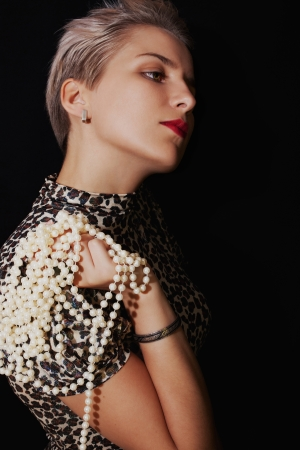 Portrait of  beautiful young woman with  pearl necklace on black background photo