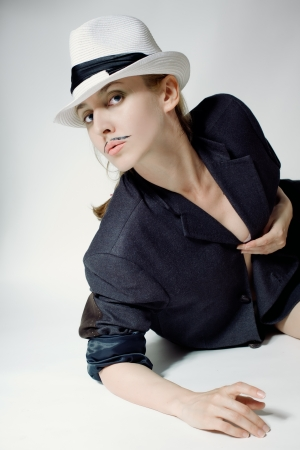 Portrait of a young woman in a hat with a fake mustache on white background photo