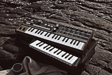 Music synthesizer lying on rocks close up Stock Photo