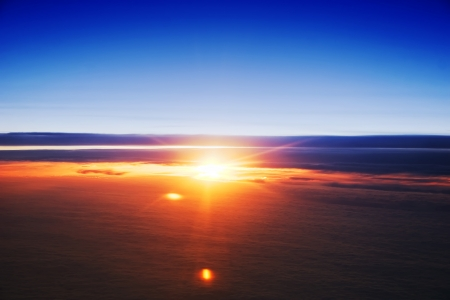 Spectacular view of a sunset above the clouds from airplane  photo