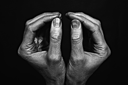 gesticulate: Strong male hands in silver paint on black background