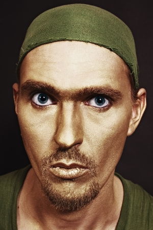 young attractive blue-eyed men with gold makeup in green headscarf closeup photo