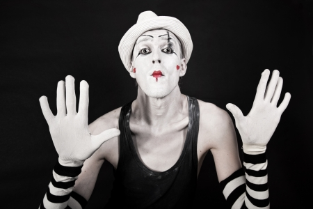 mime in striped gloves and white hat on black background Stock Photo
