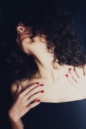 Portrait of passionate curly girl with red manicure closeup photo