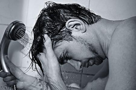 hair man: Portrait d'un beau jeune homme prend une douche gros plan