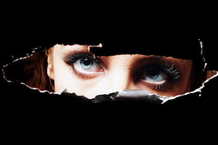 Blue eyes of young woman peeping through a hole closeup photo