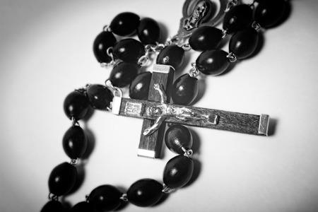 sacrosanct: Catholic black wooden beads with metal crucifix on white background Stock Photo