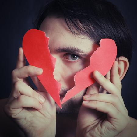 corazon roto: Retrato de un hombre joven sosteniendo un papel con el corazón roto primer plano
