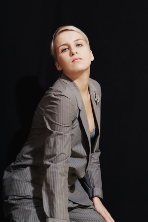 Young woman in suit and bra on black background photo