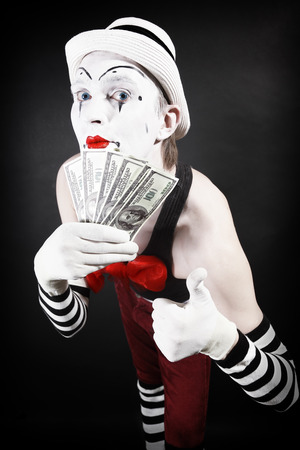 theatrical mime with dollars in their hands on a black background photo
