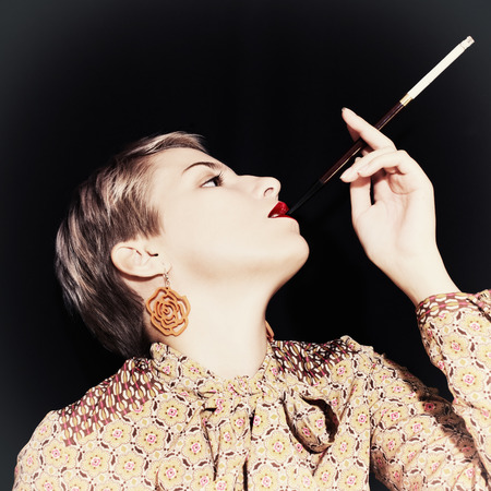 Retro portrait of young woman with  cigarette on black background