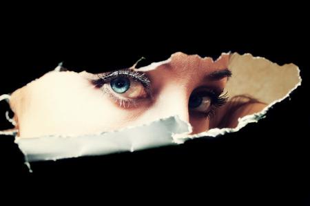 Blue eyes of young woman peeping through a hole closeup photo