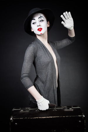 mimo: Mime de la mujer en el sombrero con la maleta en el fondo negro