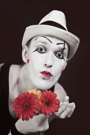 mimo: Funny mime en un sombrero blanco con bouquet de gerberas rojas sobre fondo negro