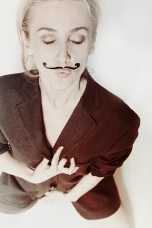 Portrait of young woman with painted mustache wearing jacket photo