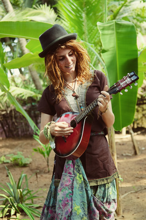 A young actress with mandalina playing against a tropical forest