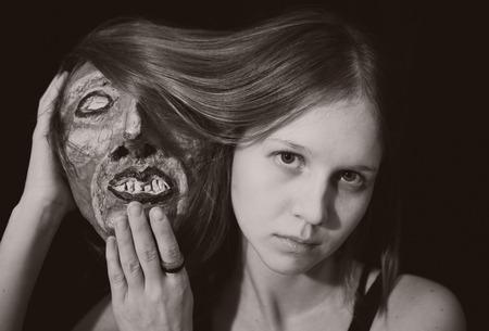papier mache: Retrato de una mujer joven con m�scara teatral espeluznante en la mano
