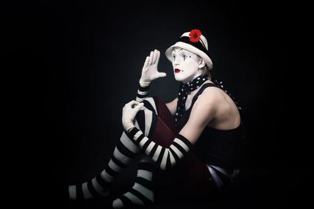 mimo: Mime divertido dram�tico en el sombrero blanco sobre fondo negro