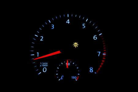 rev: Car tachometer with bright dial on a black background