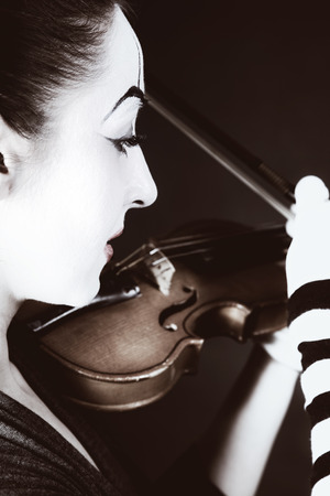 woman violin: woman  mime playing old violin on  black background