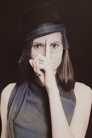 Retro portrait of a beautiful young woman in a hat with a veil on a black background photo