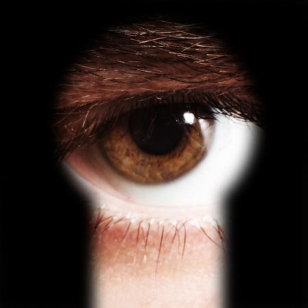 Scared male eye spying through a keyhole