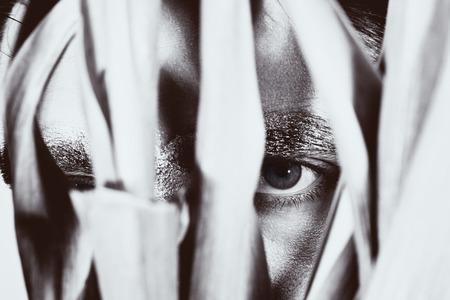 peeping: Eye peeping young man closeup