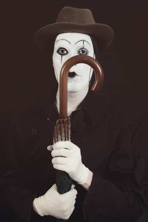 Stage actor with makeup mime in a hat holding an umbrella in his hand Stock Photo