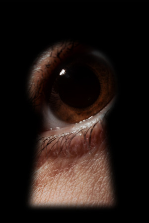 dilated pupils: Scared male eye spying through a keyhole macro Stock Photo