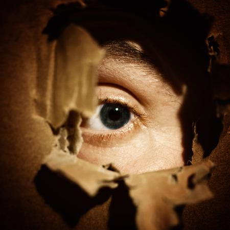 broken wall: Ojos masculinos que esp�an a trav�s de un agujero en la pared Foto de archivo