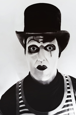 Evil clown: Portrait of a scary angry  mime wearing a tall hat Stock Photo