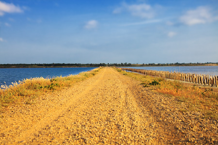 separates: Isthmus with a dirt road that separates two lakes Stock Photo