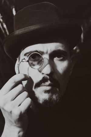 man with glasses: Retro portrait of an adult man wearing a hat and holding a pince-nez