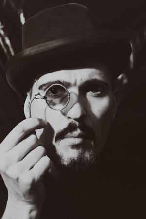 hombre con sombrero: Retro retrato de un hombre adulto con un sombrero y sosteniendo un quevedos Foto de archivo