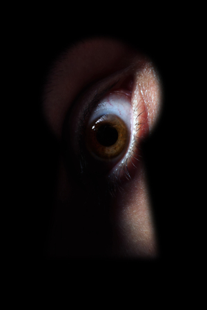 pry: Brown Male eye spying through a keyhole
