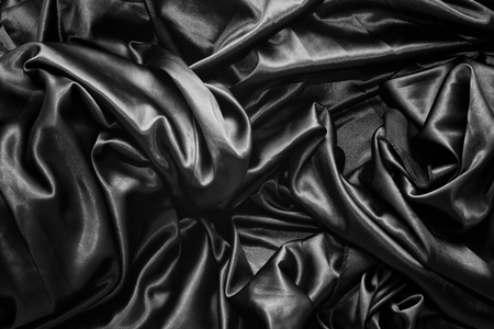 Texture of a black satin silk closeup