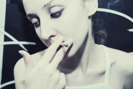 bright eyed: Portrait of beautiful young woman smoking a cigarette