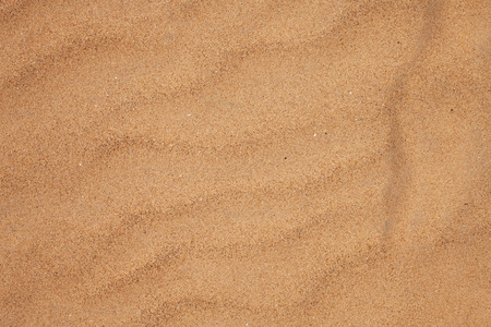 Texture of dry beach sand with wavy patterns closeup
