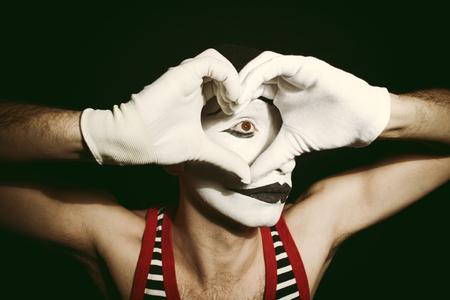 mimo: Retrato del mime triste con el corazón sobre fondo negro Foto de archivo