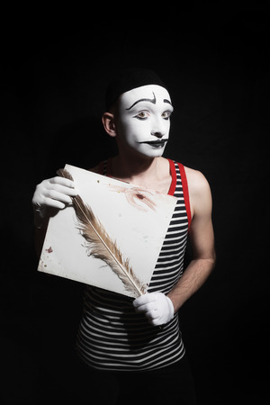 mime: Portrait of mime with quill on black background Stock Photo