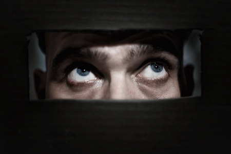 peephole: Male eyes spying through a hole in the wall