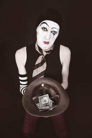 mimo: Mime con el sombrero en la mano de cerca la mendicidad