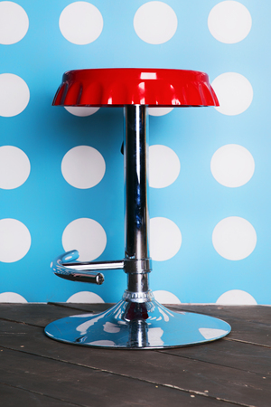 bar stool: Red bar stool against a background of wall