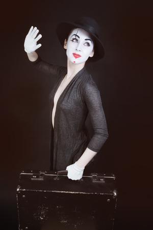 mimo: Mime de la mujer en el sombrero con la maleta sobre un fondo oscuro Foto de archivo