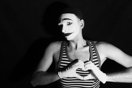 mime: Portrait of sad mime with heart on black background Stock Photo