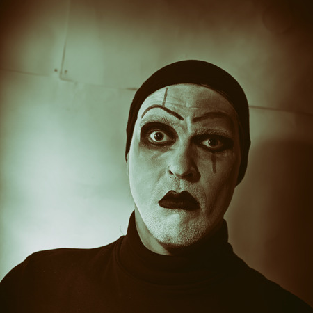 actor: Dark portrait of actor with mime makeup on her face Stock Photo